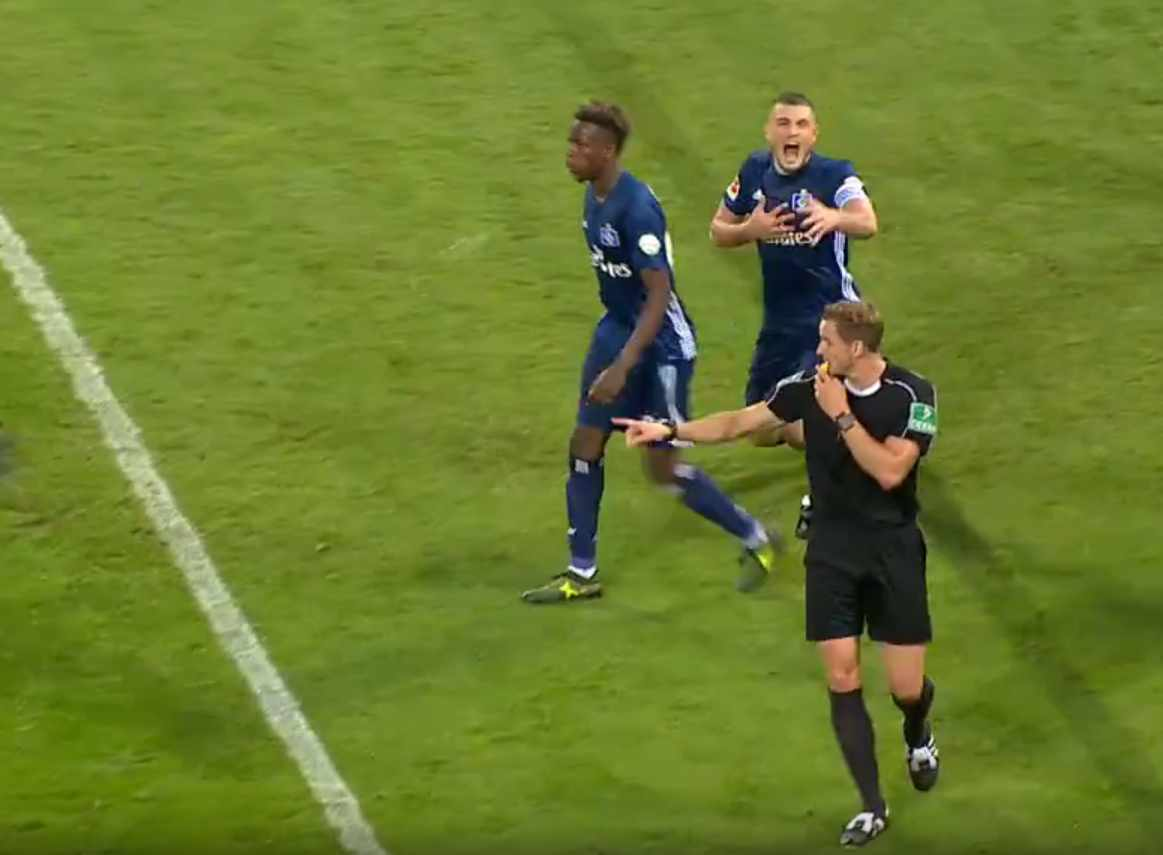 Papadopoulos falls down and grabs his chest to deceive the referee