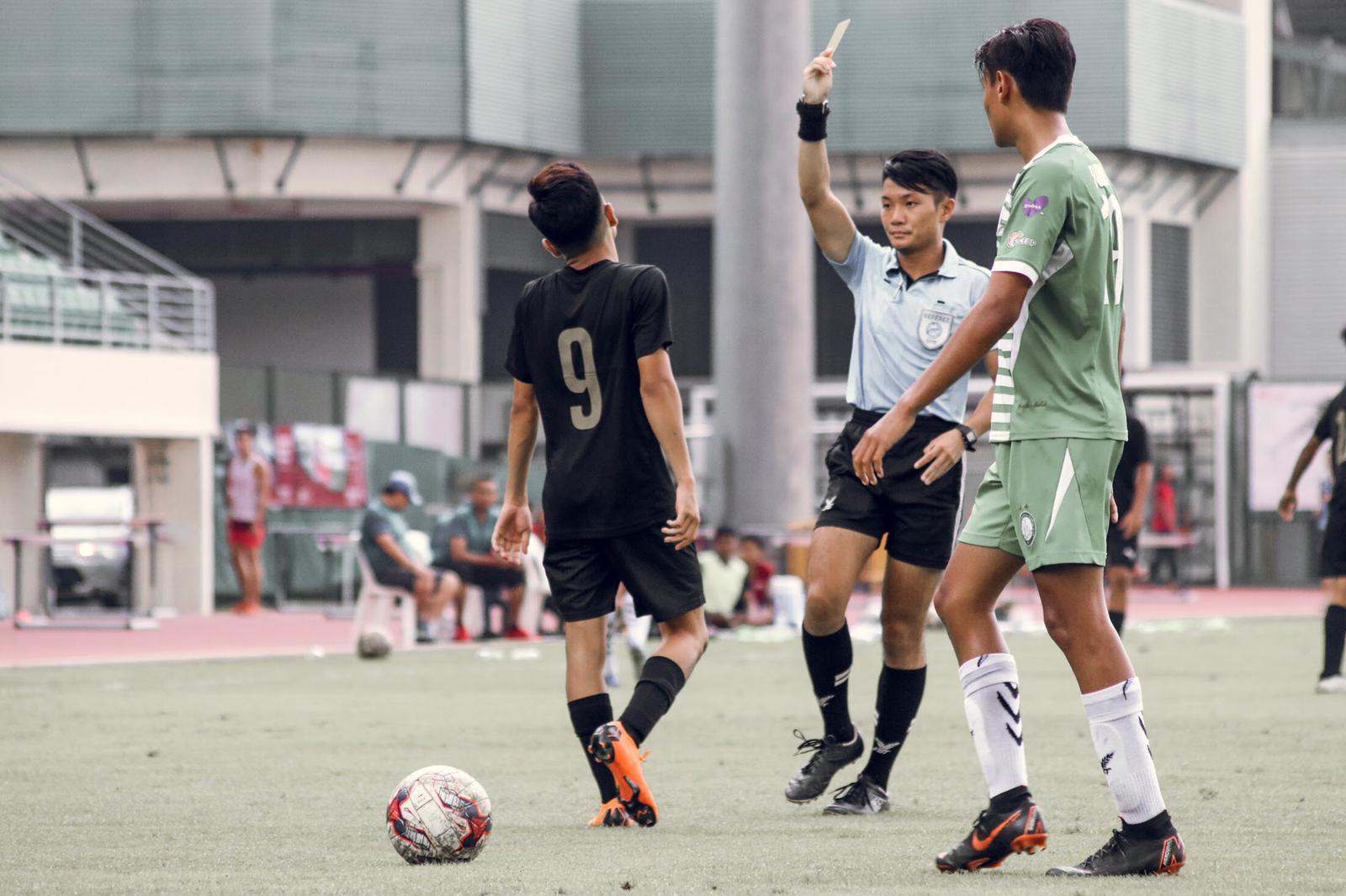 Clarence Leow showing a yellow card.